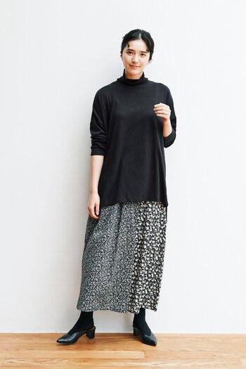 切り替えデザインの花柄スカートは、同系色の黒トップスでシックな印象に。足元も黒で揃えているので、インパクトのある柄スカートも落ち着いた印象で着こなせます。