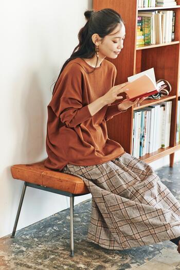 グレーにブラウンカラーが入ったチェック柄のスカートに、ブラウンのトップスを合わせたコーディネート。ボトムスに入っているカラーを選べば、簡単に統一感のある着こなしに仕上がります。