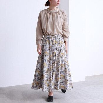 薄いベージュの花柄スカートに、ベージュのブラウスをタックイン。女性らしい落ち着いたテイストで、柄スカートを上品にコーディネートしています。足元は黒のフラットシューズで、柔らかなカラーリングに引き締めカラーをプラス。