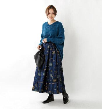 青に黄色の花柄を組み合わせたスカートに、青のニットをタックインしたコーディネート。着こなしが難しいパキっとしたカラーリングのスカートは、セットアップ感覚で同系色のトップスを合わせましょう。