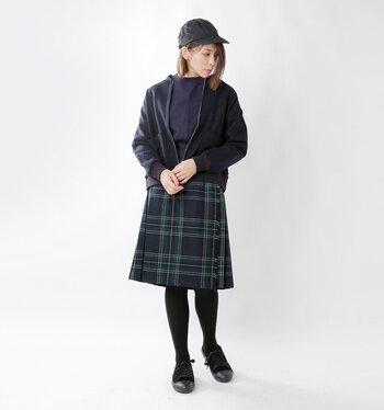 膝丈の緑×青のチェック柄スカートには、ネイビーのトップスを合わせて。黒アウターとキャップで全身を引き締めれば、チェック柄スカートをクールに着こなせます。