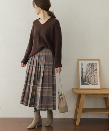 薄いブラウン系のチェック柄プリーツスカートに、濃いブラウンのニットトップスをタックインしたコーディネート。濃さの違いがあっても、トーンカラーを合わせればまとまりのある柄スカートコーデが楽しめます。