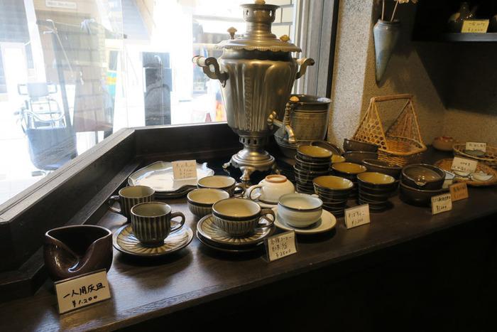 """お店の入口付近に並んでいるのは、""""小石原焼""""という、福岡県で作られている陶器です。お店で提供されるコーヒーも、こちらの小石原焼に注がれています。もしもお気に入りの食器を見つけたら、お店に訪れた記念としてお土産にいかがでしょうか。"""