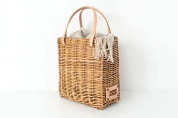 きれいめな印象を持つスクエアかごバッグには、似通ったテイストの小物がなじみやすいです。専用の被せ布や、ストールを上部に添えて目隠しを。素材の風合いで楽しむアレンジが、美しくまとまりますよ。
