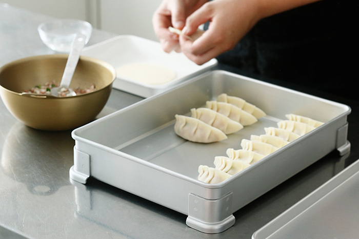 ホテルの厨房などで使われる業務用のアルミの調理器具を手掛ける「中尾アルミ」のアルミのバット。四つ角にしっかりと付けられている脚のおかげで、スタッキングしてもずれることなくいくつも重ねられます。