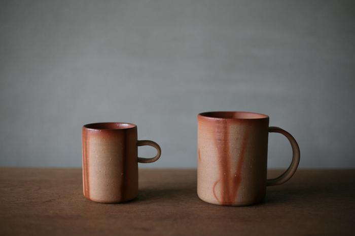 焼いた土の色合いがいい味を出している、備前焼のカップ。藁を巻いて焼くと、燃えた所が独特の模様を描きます。左は容量180mlのハイカップ、右は300mlのマグカップです。