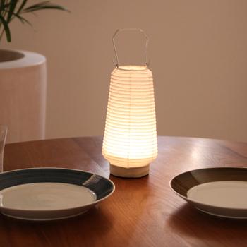 伝統工芸品指定である美濃和紙で作られたテーブルランプ。 付属の単3乾電池で点灯し、ふんわりと和紙を通した優しい光が落ち着いた空間を演出します。 食卓に、デスクにと、気軽に移動させて、和の趣のある光を楽しんでみてはいかがでしょうか。