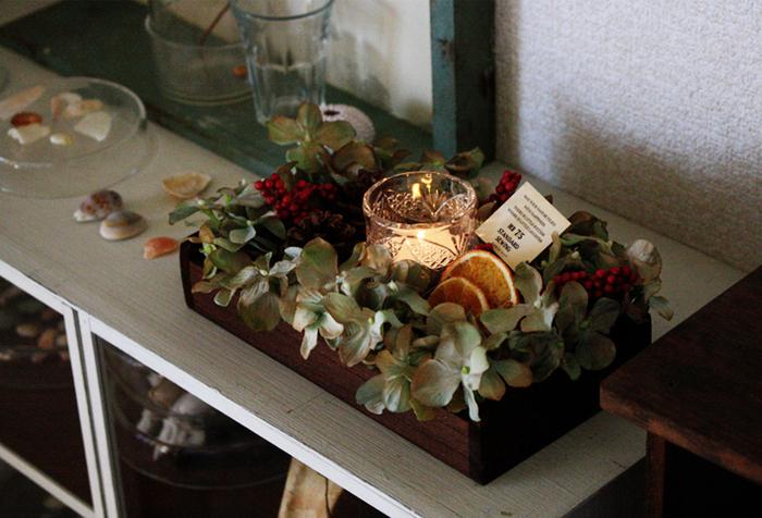 ウッドケースに造花のお花や木の実、グリーンをセットし、真ん中にグラスを。寒い季節の夜にぴったりな、シックで落ち着いた雰囲気でキャンドルを楽しむことができそうです。
