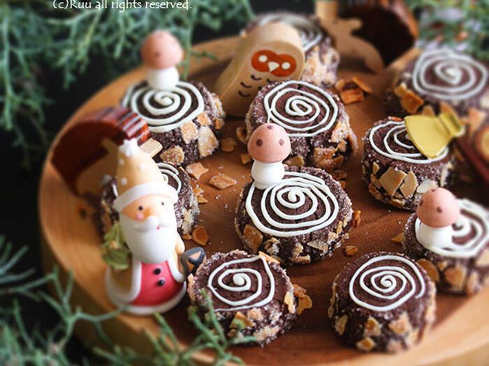 普段はお菓子作りをしないからわざわざ型を買いたくないなぁと思っている人もいることでしょう。  こちらは、ブッシュドノエル風の切り株クッキー。棒状にしたココアクッキーにアーモンドスライスとザラメをまぶしてスライス。焼き上げた後にホワイトチョコペンで年輪を描きます。  型がなくてもクリスマス風のクッキーが作れるなんて嬉しいですね。