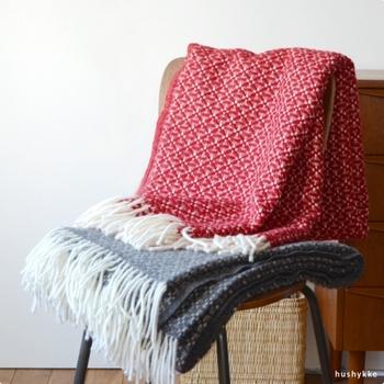 生後6ヶ月以内の羊からとれるやわらかなラムウールを100%使用した「スロー」。ブランケットよりも空気を多く含ませた編み方をしているからふんわり軽く、足元にかけたり、肩に掛けてまとったり、ベッドにふわりと掛けたりといろいろな使い方で楽しめます。落ち着いた色合いの深いレッドに、レトロ感ある織柄も素敵。