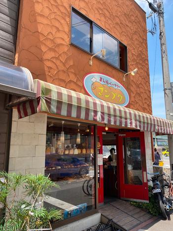 「マンプク」の看板と真っ赤なドアが目印の、「まん福ベーカリー」。大阪メトロ北浜駅から徒歩4分ほどの、土佐堀川沿いにたたずむお店です。よく行列ができる人気店ですが、お値段はとってもリーズナブル。あんぱん、クリームパン、メロンパンなど、よく知ったラインナップが並びます。