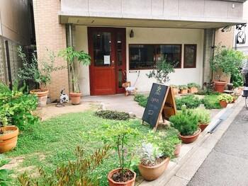 大阪メトロ中崎町駅より徒歩2分。ビルの1階に入っている「Boulanger S.KAGAWA」は、赤いドアが目印のパン屋さん。お店の前には、青々とした芝生に鉢植えがずらりと並ぶ、かわいらしいお庭が広がっています。せっかくお出かけするのなら、緑あざやかなお庭をながめながら、美味しいパンをほお張る素敵なひとときにしてみませんか?