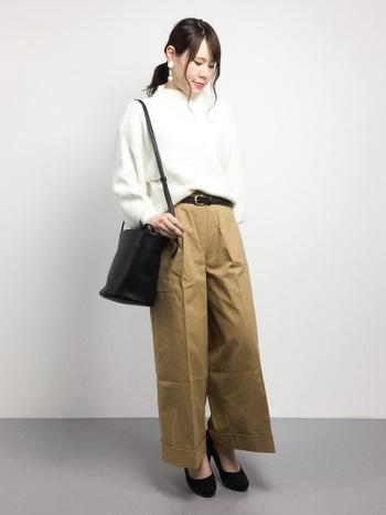 少し厚手の素材が恋しくなる秋の季節。  こちらは、パリっとしたハリのある綿混素材のベージュパンツに、白いニットセーターを合わせたスタイリング。ベルトやパンプス、バッグは黒で統一して、引き締め役に。バランスのよい着こなしです。