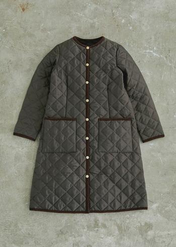 「ARKLEY」と同じく、ブランドの定番アウターであるロング丈のノーカラーキルティングコート「ARKLEY LONG(アークリー ロング)」。細身で美しいシルエットが特長です。こっくりとしたブラウンカラーが、スタイリングに奥行きを与えてくれる一着。