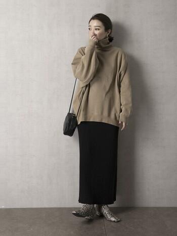 同じくベージュ×黒のタイトスカートの組み合わせ。スウェットがタートルなので、より縦長効果を発揮。ロング丈のタイトスカート×ヒールブーツ、ポシェットで、レディライクな雰囲気に仕上がっています。