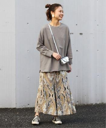 アースカラーのスウェットと相性の良い色柄のスカート。どちらもくすみカラーなので、派手になりすぎず大人コーデに。 裾がふんわりとしたスウェットは、ロング丈のフレアスカートとバランスが良く、魅力を引き立てます。 シルバーのアクセント使いが素敵です♪