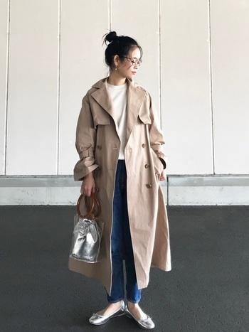 白トップス×デニムの定番コーデもオーバーサイズのトレンチコートで旬の着こなしに変身。メタリックな小物を合わせてちょっぴりスパイスをきかせるのが、おしゃれ上手にみせるコツ。
