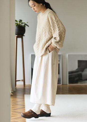 表情豊かなアランニットのセーターは、ほどよいボリューム感がありながら、編み模様を途中で止めることで、上部はすっきり。ゆるめのAラインシルエットが、編み模様の部分にほんのりドレープを作り、女性らしさも演出してくれます。やさしい風合いとすっきりとした雰囲気で、大人のかわいらしさも上品さも引き立ててくれます。