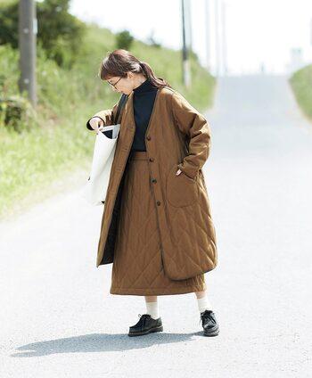 薄めの中わたを入れたトレンドのキルティングコートは、一枚仕立てで軽い着心地だからデイリーに大活躍!ウール混ならではのムラ感があるシックな表地に、深みのあるコーデュロイのパイピングでメリハリをつけ、ほどよく全体を引き締めるアクセントに。ノーカラーですっきりスタイリッシュに着こなせるところもうれしい。同素材のスカートと合わせてセットアップとして楽しむことも。