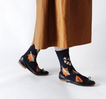 トレンドの暖色靴下は、ワンカラーで楽しむほかに柄で取り入れるアイデアも。秋らしさたっぷりのリーフソックスは、足元を眺めるたびにほっこりできそうですね。