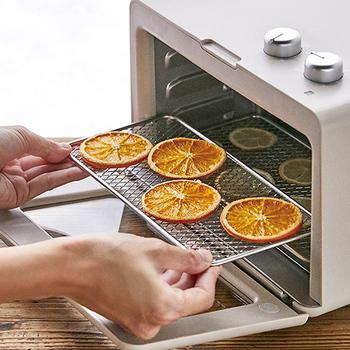 ⑤オレンジを乾燥させる  シロップを軽く拭き取ったオレンジを天板に並べ、100度に設定したオーブンで40〜50分焼いていきましょう。途中で1度、裏表をひっくり返します。  クーラーの上にオレンジを移動させてしっかり乾かせば、セミドライな本格ドライオレンジの完成!