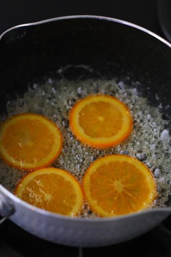 ③オレンジを煮る 水と2/3の量のグラニュー糖をオレンジの鍋に入れ、中火にかけます。沸騰したら落とし蓋をして、弱火で15分〜20分程度煮詰めていきましょう。  火を止めたら残りのグラニュー糖を全体にふりかけ、再度落とし蓋をしてシロップが完全に冷めるのを待ちます。
