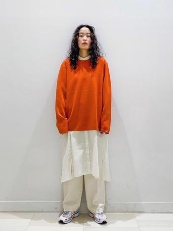 オレンジニットにロングシャツを重ねたコーディネート。ロングタイプの白シャツを合わせることで気になる足回りをカバーでき、スタイルアップ効果も狙えますね。