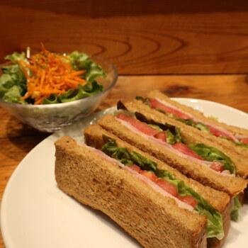 下町の名店の食材を使ったメニューが人気です。こちらは千駄木にある「コシヅカハム」のハムとレタス、トマトを使ったライ麦サンドです。シンプルなサンドイッチは、素材の味がしっかりと楽しめると評判。同じくコシヅカハムのコンビーフトーストや、浅草の名店「ペリカン」のパンを使ったトーストもおすすめですよ。