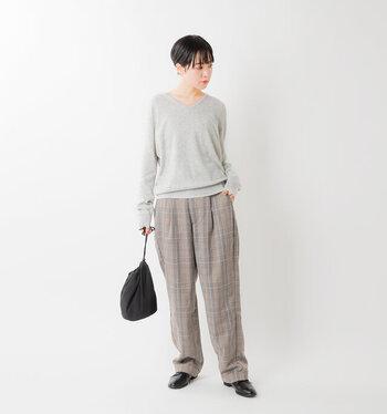 薄いグレーのVネックニットに、ブラウンのチェック柄パンツを合わせたスタイリング。ゆったりシルエットでリラックス感がありますが、黒の巾着バッグとシューズでさりげなく引き締め感をプラスしているのがポイントです。