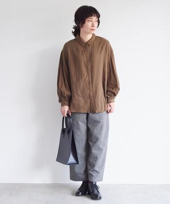 ブラウンのブラウスに、グレーのワイドパンツを合わせたスタイリングです。タックインしてきっちり感のあるコーディネートにもできますが、あえて裾を出すことでブラウスをナチュラルな印象で着こなしています。足元は、ラフになり過ぎないよう黒のシューズをチョイス。