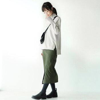薄いグレーのタートルネックニットに、カーキカラーのタイトスカートを合わせたコーディネート。足元や小物を黒で揃えることで、カジュアルになり過ぎない大人っぽさを演出できます。