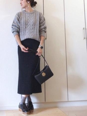 ざっくりとしたケーブル編みのグレーニットを、黒のタイトスカートにゆるくタックインしたコーディネート。足元はグレーの靴下×黒シューズで、全身をグレー×黒のカラーリングでまとめています。カジュアルなニットを、女性らしく着こなしたスタイリングです。