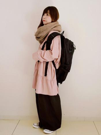 ピンクのブラウスに、黒のゆったりワイドパンツを合わせたミックスコーデ。女性らしいトップスを、黒のリュックやスニーカーを合わせて、上手にカジュアルダウンしています。首元にボリュームたっぷりのネックウォーマーを巻いて、全体的にラフな着こなしに。