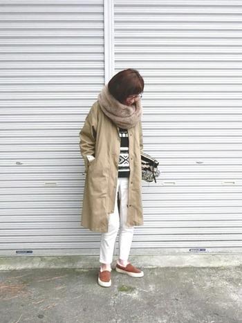 ベージュのコートにベージュのネックウォーマーを合わせて、統一感のある着こなしにまとめています。柄トップスが印象的な組み合わせですが、コートから少しだけ覗かせることで派手になり過ぎていません。
