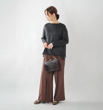 濃いグレーのプルオーバーに、ブラウンのワイドパンツを合わせたコーディネート。パンツと合わせたカラーのシューズとショルダーバッグで、ナチュラルながらも女性らしい印象にまとめています。