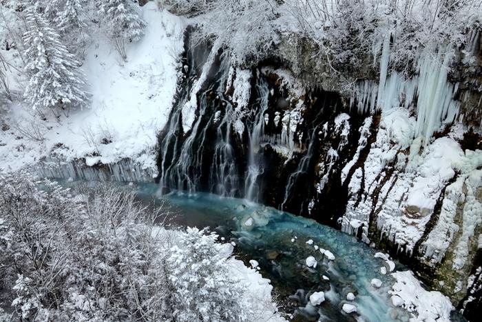 白ひげの滝は、北海道美瑛町、白金温泉郷にある落差30メートルの滝です。標高600メートルの位置にある白ひげの滝は、地下水が溶岩層などの裂け目から落ちる潜流瀑という珍しい滝です。滝の下流に流れる川はコバルトブルーに輝いており、氷瀑の美しさを引き立てています。
