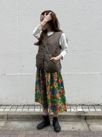 レトロでハッピーなオーラが漂う柄スカートに、茶色のダウンベストを合わせて。BOHOシックな雰囲気もあって、素敵です。