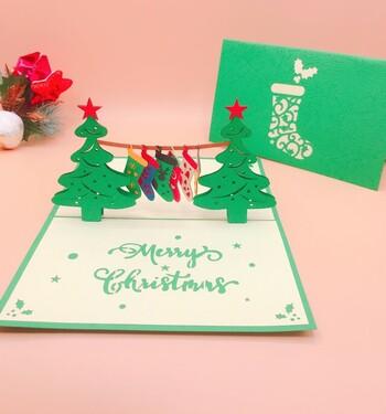 靴下のラッピングに靴下のポップアップグリーティングカードを添えてはいかがでしょうか。切り紙のポップアップカードを開けると、2本クリスマスツリーと、五足のカラフルなクリスマスの靴下が飛び出して来ます。