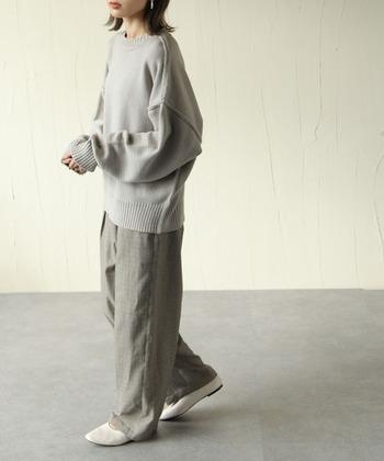 薄いグレーのニットに、グレーのチェック柄ワイドパンツを合わせたワントーンコーデ。メンズライクにも見えるベーシックな着こなしは、足元に白パンプスをチョイスすることで女性らしさをさりげなくアピールしているのがポイントです。