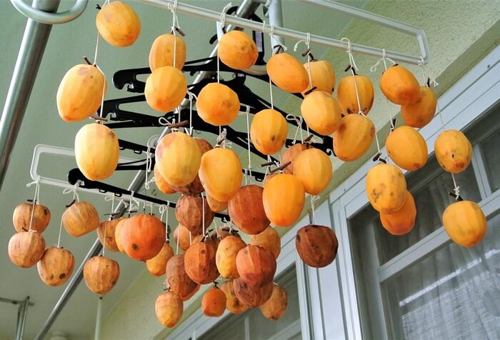 ハンガーなどに吊るし、軒下の風通しのよい場所に干します。このとき、柿同士がくっついてしまうと、カビの原因になってしまうので、くっつかないように間隔をあけて干します。