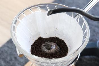 """お湯を2回に分けて注いでいきます。最初のお湯は、美味しいドリップコーヒーの要となる""""蒸らし""""です。  1.サーバーに数滴落ちる程度の少量のお湯を注ぐ 2.豆のガスが抜ける様子を見つつ1分ほど待つ  粉の近くから、そっと優しくお湯を注いでくださいね。"""