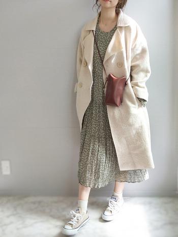 ふんわりした白のチェスターコートに甘めのプリーツワンピを合わせたコーデ。足元の肌見せやスニーカーを合わせることで適度にカジュアルダウンして着こなしています。寒い季節でもほっこりした雰囲気を演出できるスタイルです。