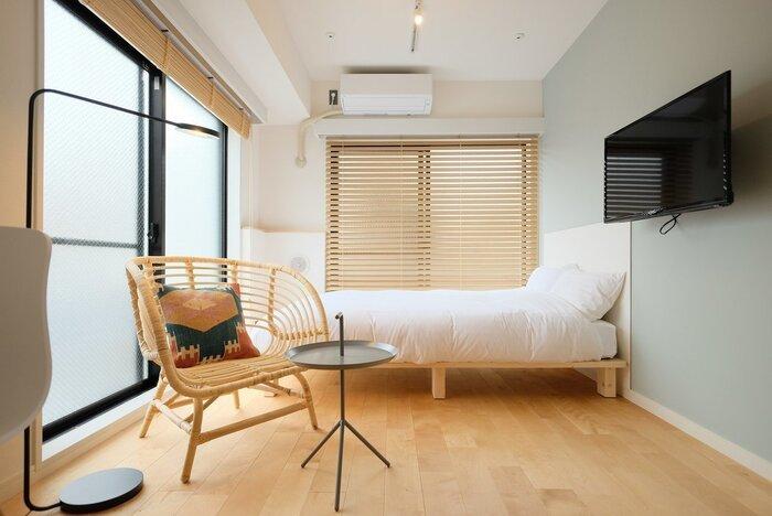 ベッドリネンの白×明るいブラウンの家具により、ナチュラルで清潔感のあるベッドルームになっています。チェアに置かれたクッションがお部屋に良いアクセントを与えています。シンプルな空間にも馴染みやすいデザインのクッションカバーがおしゃれですね。テレビも床に置かず壁に浮かせて設置することで空間が広く見えますし、ベッドルームのお掃除も楽そうです。