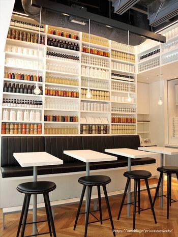 二重橋スクエアの1階にある「Made in ピエール・エルメ 丸の内」は、日本全国の生産者とコラボレーションした食料品や雑貨、ファッションアイテムなど、日本の素晴らしいものを丸の内から世界へ発信しています。  併設のカフェは、モノトーンを基調としたスタイリッシュな雰囲気で、天井まである棚に並ぶドレッシングやジャムのボトルがインテリアのアクセントになっています。