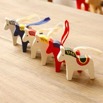 """こちらは、白樺で作られた手のひらサイズの馬のオーナメント。スウェーデンで""""幸福を呼ぶ馬""""とされる「ダーラヘスト」がモチーフです。そのまま置いてもいいし、紐が付いているのでクリスマスツリーに吊るすこともできますよ♪"""