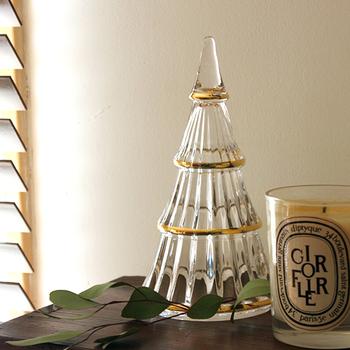 「HOLMEGAARD(ホルムガード)」は、1825年に創業したデンマークの老舗ガラスブランドです。王室御用達ブランドにも選ばれたクオリティの高さが特徴。美しく繊細なデザインがクリスマスにもぴったりです。  こちらは、ガラス素材のクリスマスツリー。透明感とゴールドの枠がとってもゴージャスで大人の雰囲気です。内側にウエーブが施されていて、光が屈折するので、キャンドルの近くに置くとライトアップをさらに素敵に演出してくれます♪