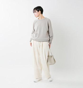 薄いグレートップスに、白のゆったりパンツを合わせたコーディネート。バッグはトップスに、スニーカーはボトムスに、それぞれ色を合わせています。カジュアルながらもナチュラルな印象で、大人のデイリーコーデにぴったりな着こなしですね♪