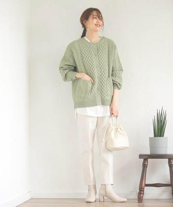 グリーンのニットカーディガンに、白のテーパードパンツを合わせたコーディネート。カーディガン以外はすべて白で揃えて、ヒールやレイヤードで女性らしい着こなしに仕上げています。