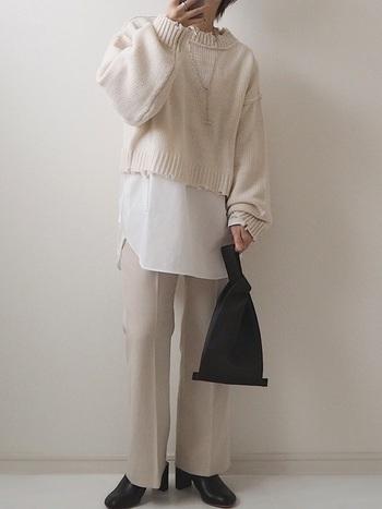 白のショート丈ニットに、白系のワイドパンツを合わせたコーディネート。インナーに白シャツを合わせて、ワントーンのレイヤードスタイルにまとめています。バッグとブーツはどちらも黒で揃えて、ニュアンス感のあるモノトーンコーデに。