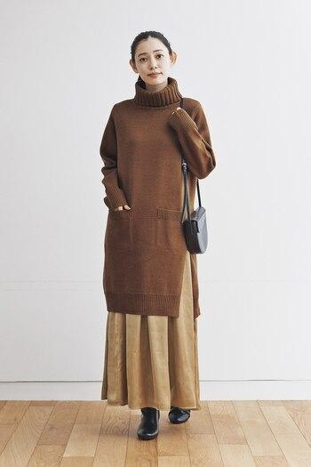 ブラウンンのタートルネックチュニックに、ベージュのスカートを合わせたスタイリング。スリットが入ったデザインのトップスなら、スカートとのレイヤードがおしゃれにキマります。バッグやブーツは黒で揃えて、大人な雰囲気に。